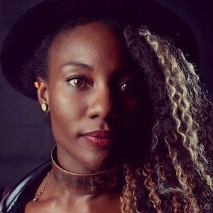 A Black woman looks at the camera. She has wavy blond hair and wears a black hat. She has a gold-disc earring, and wears a band around her neck. The left side of her face is in shadow.
