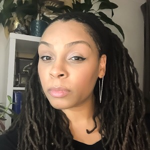 A Black woman with a V-shaped earring looks at the camera. She has long dreadlocks. Behind her, a bookcase, on which two potted plants sit.