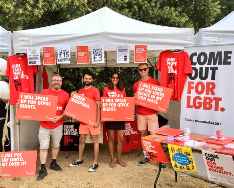 Four people at a Stonewall stall in red t-shirts holding up red placards including 'I will speak up for QTPOC rights', 'Queer diaspora', 'I will stand up for LGBTQ rights in my faith space'.