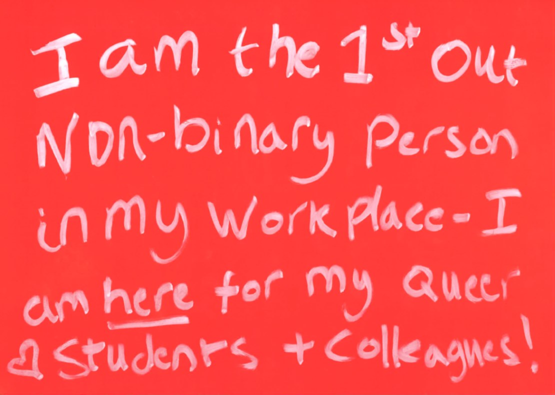 Red placard which says 'I am the 1st out non-binary person in my workplace - I am here for my queer students and colleagues.'