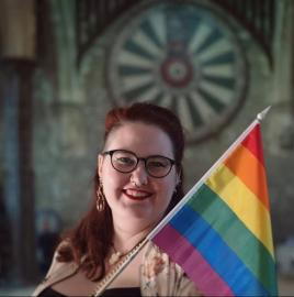 Person smiling and there's a rainbow flag