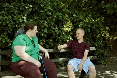 Two individuals sat on a bench talking