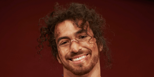 A man smiles at the camera. He has curly brown hair, a wide grin, and a plaster on the bridge of his nose.