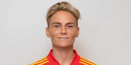 Jess Fishlock standing against a blank wall and smiling