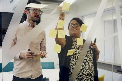 Two people discuss ideas while sticking up post it notes on a glass wall.