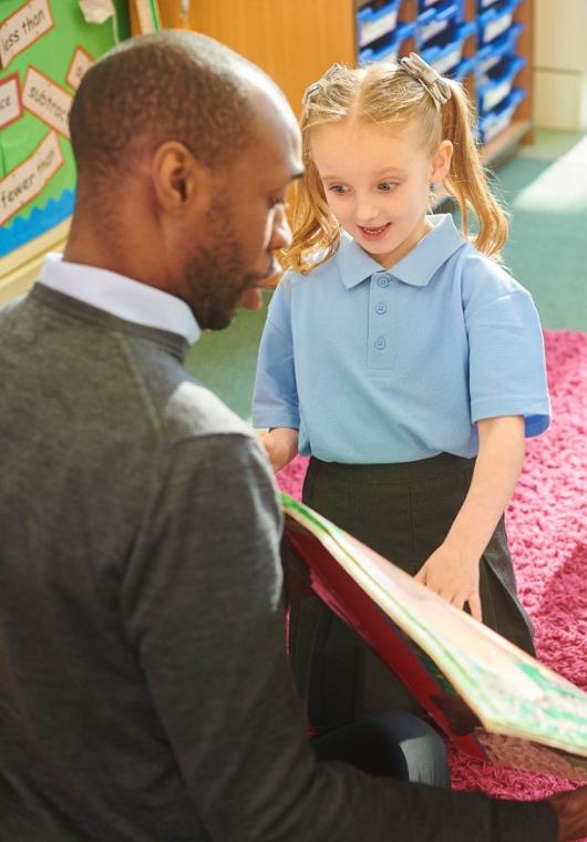 A teacher showing a book to a child