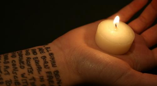 Candle in palm of hand and text from The Universal Declaration of Human Rights