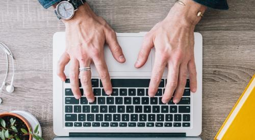 Pair of hands typing on a laptop keyboard