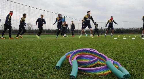Giant rainbow lace on football pitch with players in the background