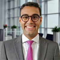 Person smiling in a suit and tie in a professional office