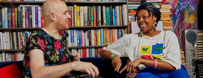 Two people sat talking on a sofa in front of bookshelves