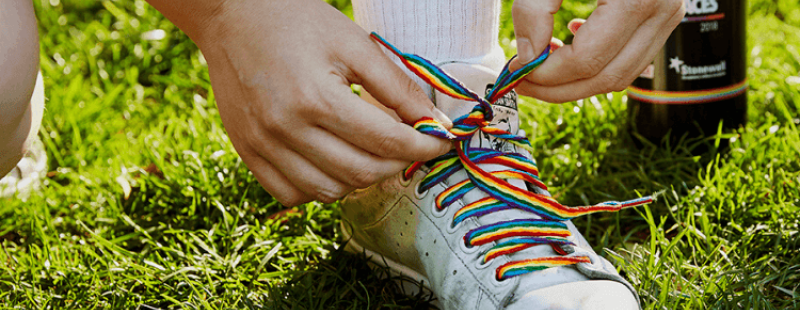Person wearing rainbow laces in shoes