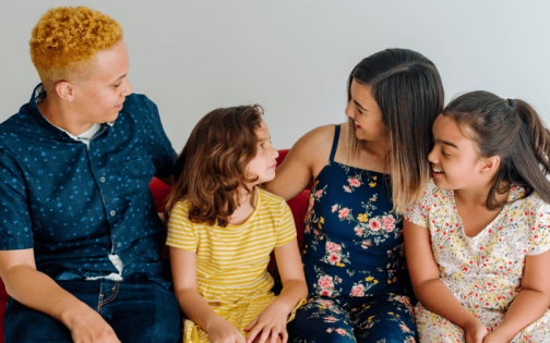 A family sits on a red sofa speaking to each other, against a white background