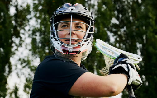 Person holding a lacrosse bat in a field