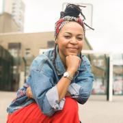 A Black woman on one knee in a concrete playground. She looks at the camera, has a hand propped beneath her chin, and wears a denim jacket and red trousers. Her hair is worn up, and a bandanna is tied around her head.