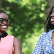 Two people of colour smiling and holding hands in a leafy, park-like environment.