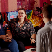 Group of people sitting together in a community centre. There are flags and pink drapes behind them.