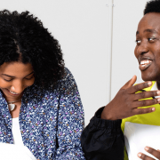 Young people of colour sit at a table inside and talk and laugh