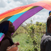 Two Black people with a rainbow flag in a field