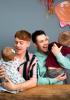 2 dads holding their children
