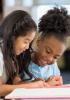 Two girls in school uniform sharing a book