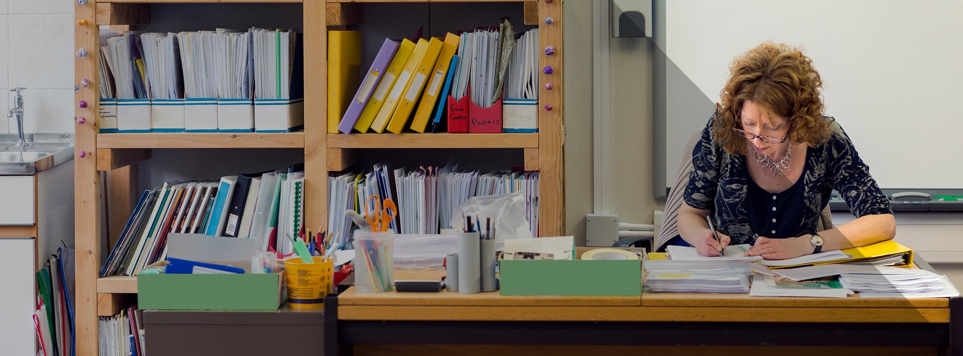 Schoolteacher sitting at desk and marking work