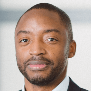 Black man in a business suit looks at the camera against a blurred background