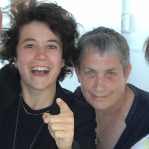 Two white women, one younger, one older, look at the camera, which is looking down on them. The younger woman points her finger at it and is smiling