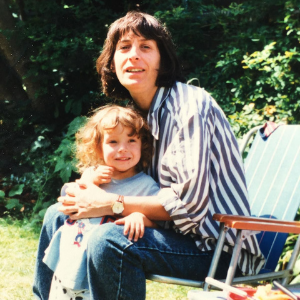 A white mother and child outside. The mother is sitting in a chair, the child is against her knees.