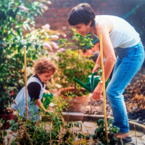 A white mother and child in a garden, tending flowers in sunshine. The picture is taken on old-style film, denoting that it's an old photo