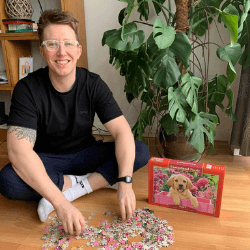 Person doing a jigsaw of a pink dog
