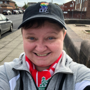 Smiling woman with a Liverpool Football Club cap