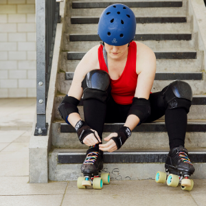 Woman sitting on stairs tying up roller skates with rainbow laces