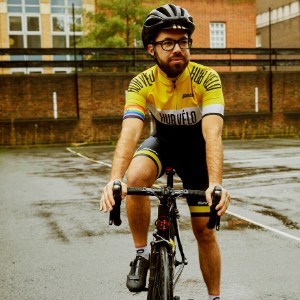 Man on bike in a wet car park