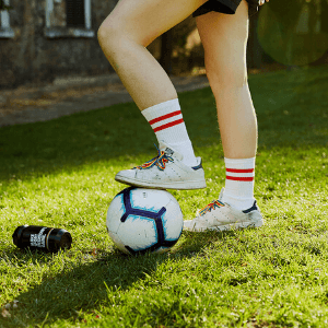 Legs on football in shoes with rainbow laces